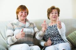 Счастливые старшие женщины представляя внутри помещения и смеясь над Стоковые Фото