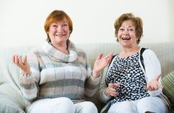 Счастливые старшие женщины представляя внутри помещения и смеясь над Стоковое Изображение RF