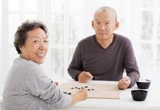Счастливые старшие пары играя шахмат в живущей комнате стоковые фото