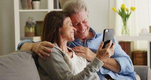 Счастливые старшие пары используя smartphone на кресле Стоковые Фотографии RF