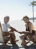Счастливые старшие пары на Deckchairs на пляже Стоковые Фото