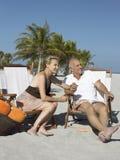 Счастливые старшие пары на Deckchairs на пляже Стоковая Фотография
