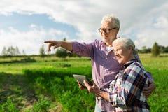 Счастливые старшие пары с ПК таблетки на лете обрабатывают землю стоковые фото