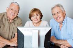 Счастливые старшие друзья используя компьютер в классе стоковые изображения rf