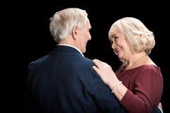 Счастливые старшие танцы пар и смотреть один другого на черноте стоковое изображение