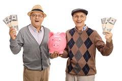 Счастливые старшии с пачками денег и piggybank Стоковые Изображения