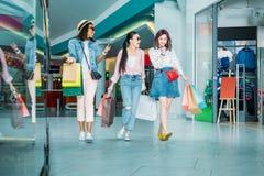 Счастливые стильные молодые женщины с хозяйственными сумками идя в торговый центр Стоковое фото RF