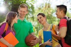 Счастливые студенты в парке стоковая фотография