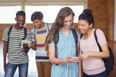 Счастливые студенты используя мобильный телефон и цифровую таблетку в кампусе Стоковое Фото