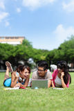 Счастливые студенты колледжа используя компьютер Стоковое Изображение
