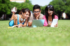 Счастливые студенты колледжа используя компьютер Стоковые Фото
