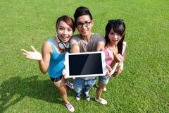 Счастливые студенты показывают цифровую таблетку Стоковые Изображения