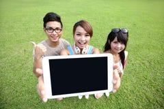 Счастливые студенты показывают цифровую таблетку Стоковая Фотография