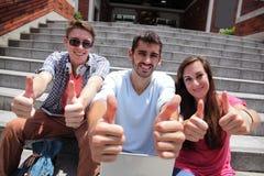Счастливые студенты показывая большой палец руки вверх стоковая фотография