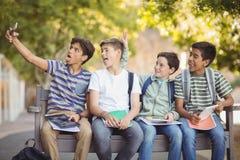 Счастливые студенты сидя на стенде и принимая selfie на мобильный телефон Стоковые Фотографии RF