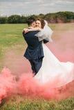 Счастливые танцы пар в красном дыме на луге Стоковые Фотографии RF
