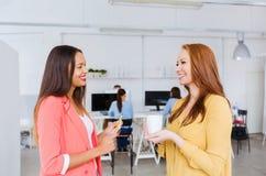 Счастливые творческие женщины говоря на офисе Стоковое Фото