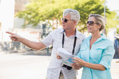 Счастливые туристские пары используя карту в городе Стоковые Фотографии RF