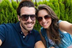 Счастливые туристские пары принимая selfie в городе стоковая фотография
