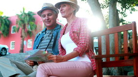 Счастливые туристские пары сидя на стенде держа карту сток-видео