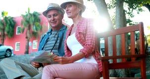 Счастливые туристские пары сидя на стенде держа карту видеоматериал