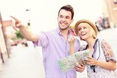 Счастливые туристы sightseeing город с картой Стоковая Фотография