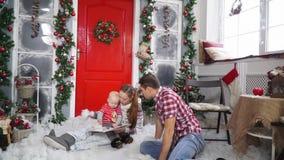 Счастливые усаживание и чтение семьи книга рядом с красиво украшенной дверью акции видеоматериалы