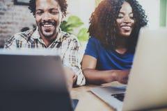 Счастливые усмехаясь Афро-американские пары работая совместно дома Молодой чернокожий человек и его подруга используя компьтер-кн Стоковые Фотографии RF