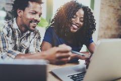 Счастливые усмехаясь Афро-американские пары работая совместно дома Молодой чернокожий человек и его подруга используя компьтер-кн Стоковое Изображение RF