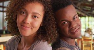Счастливые усмехаясь Афро-американские человек и женщина полагаются на одине другого по мере того как они представляют для портре Стоковая Фотография RF