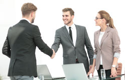 Счастливые усмехаясь бизнесмены тряся руки после дела в offi Стоковое Фото