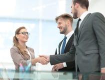 Счастливые усмехаясь бизнесмены тряся руки после дела в offi Стоковое фото RF