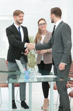 Счастливые усмехаясь бизнесмены тряся руки после дела в offi Стоковое Изображение RF