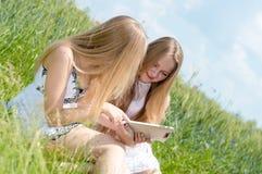 Счастливые усмехаясь девушки и планшет Стоковые Фотографии RF