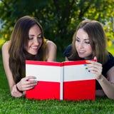 Счастливые усмехаясь девушки с книгой Стоковая Фотография