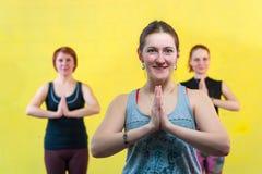 Счастливые усмехаясь женщины практикуя йогу в классе Стоковое Фото