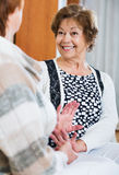 Счастливые усмехаясь зрелые женщины сидя на софе Стоковые Изображения RF