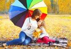Счастливые усмехаясь мать и ребенок при зонтик сидя совместно на шотландке в солнечной осени Стоковое Фото