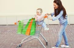 Счастливые усмехаясь мать и ребенок с тележкой и хозяйственными сумками вагонетки Стоковое Фото