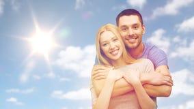 Счастливые усмехаясь пары обнимая над небом и солнцем Стоковая Фотография