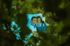 Счастливые усмехаясь пары ослабляя на зеленой траве ванта Стоковые Фотографии RF