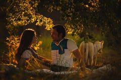 Счастливые усмехаясь пары ослабляя на зеленой траве внутри Стоковые Фото