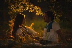 Счастливые усмехаясь пары ослабляя на зеленой траве внутри Стоковая Фотография