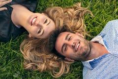 Счастливые усмехаясь пары ослабляя на зеленой траве Парк Молодые пары лежа на траве напольной Элегантно одетый Стоковое фото RF
