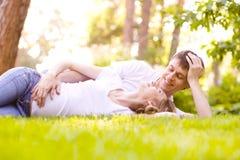 Счастливые усмехаясь пары ослабляя на зеленой траве Стоковая Фотография RF