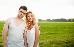 Счастливые усмехаясь пары ослабляя на зеленой траве Стоковое Фото