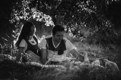 Счастливые усмехаясь пары ослабляя на зеленой траве Стоковое Изображение RF