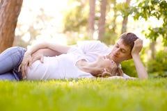Счастливые усмехаясь пары ослабляя на зеленой траве Стоковая Фотография