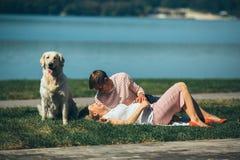 Счастливые усмехаясь пары ослабляя на зеленой траве Стоковое фото RF