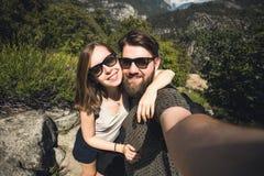 Счастливые усмехаясь пары студентов в влюбленности принимают автопортрет selfie пока пеший туризм в национальном парке Yosemite,  Стоковые Изображения RF